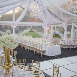Wedding reception tent with dance floor and decorated tables - The Rented Event