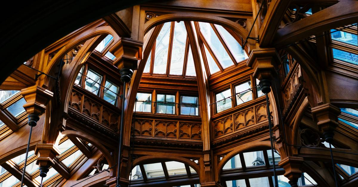 An indoor view of windows and arches in an intricate wooden building.