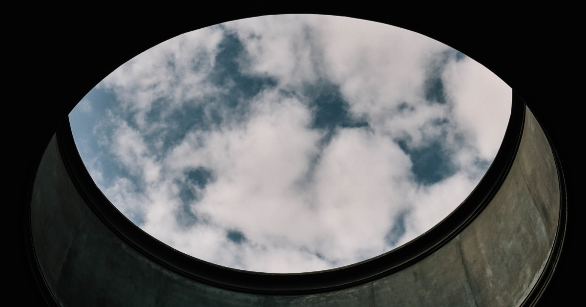 View of blue sky with puffy white clouds through a circular skylight window.