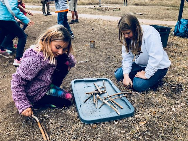 students working on a project with sticks.
