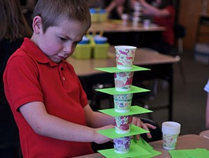 Boy intently focused on stacking paper and cups into a tower.