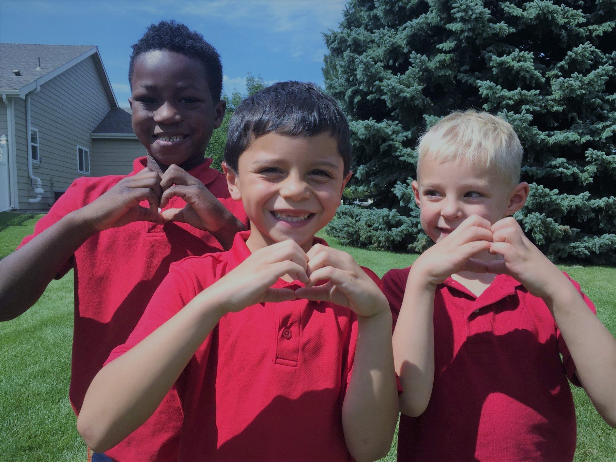 3 children smiling and making hearts with their hands.