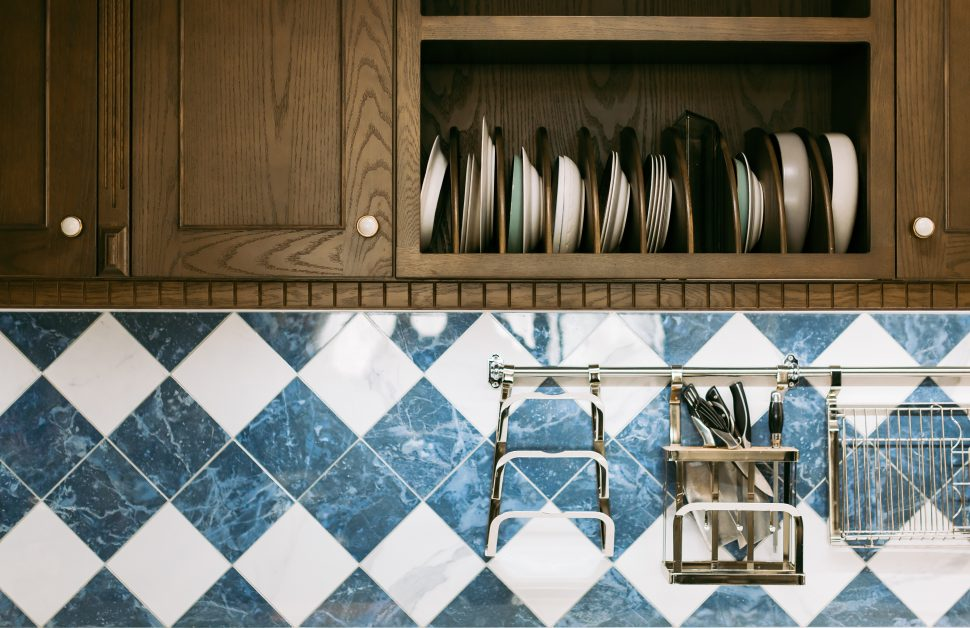 An image of a kitchen with a blue and white tile backsplash.