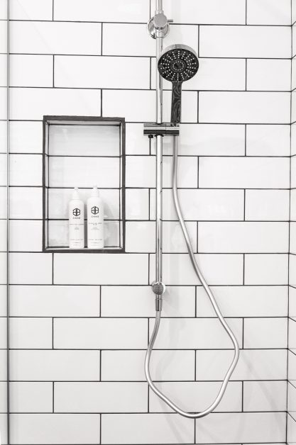 An image of the inside of a shower with black and white tile.
