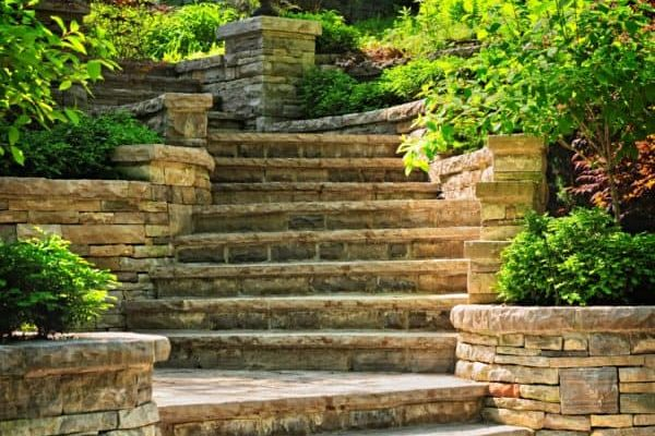 A well-crafted stone staircase is lined with plant beds.