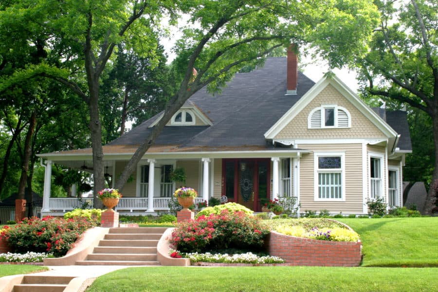 A colonial style home with a large proch is decorated with a stair-stepped set of rising flower beds.