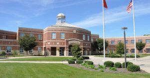 A large brick building with a simple, elegant landscape.