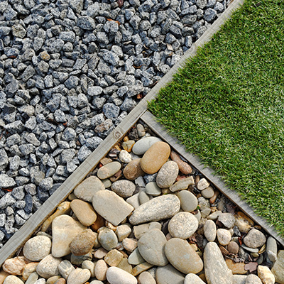 A neatly divded section of yard, with a section of turf, large rock and grey gravel.