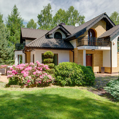 A beautiful home with a large flowering bush and a cobble stone drive.