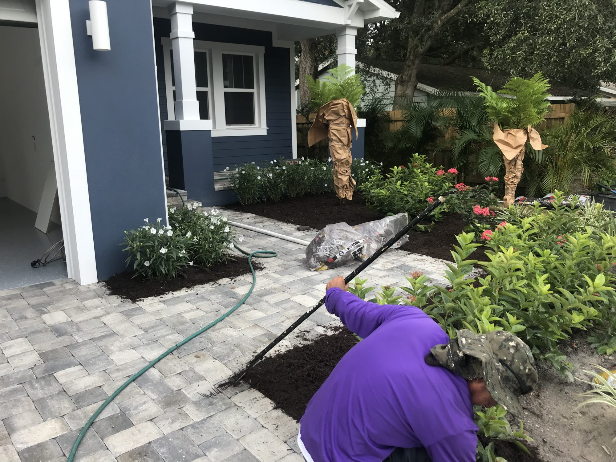 A gardener arranges mulch in a new flower bed.