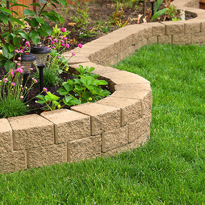 A neat retaining wall draws a line between the lawn and the raised flower bed.