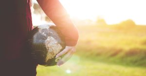 Person holding a globe of the world while looking at rural land.