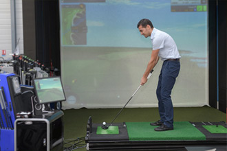 Man Golfing at Simulator