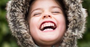 close up of child laughing with teeth showing and eyes closed
