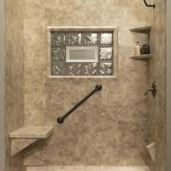 A picture of a gorgeous shower with canyon rock tile walls, a seating bench, and other amenities.