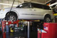 Minivan lifted up on repair stand in garage.