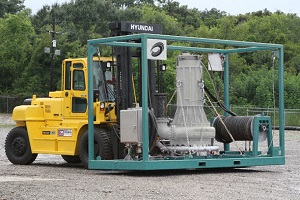A yellow forklift moves a gray electric dredge system to a work site.