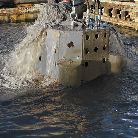 A hydraulic pump forces mud and sediment out of the top of the dredge.