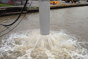 A gray pile cleaner system releases jets of water into a pond near the edge of a port.