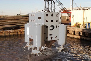 A gray hydraulic dredge made by U.S. Aqua Services is suspended over a body of water in a port.