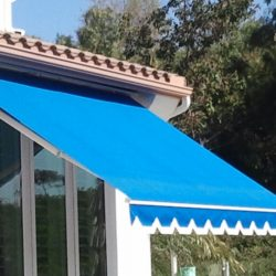 Residential retractable awning with blue awning fabric and white trim