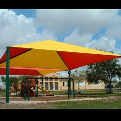 Custom tension shade with red and yellow awning fabric for a playground