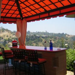 Custom cabana with red awning fabric over an outdoor bar