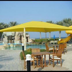 Commercial tension shade with yellow awning fabric for a pool