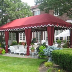 Large residential cabana with red awning fabric and drapes