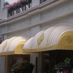 Custom storefront awning with striped yellow and white awning fabric