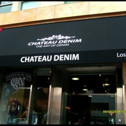 White awning graphics on a black storefront awning for Chateau Denim