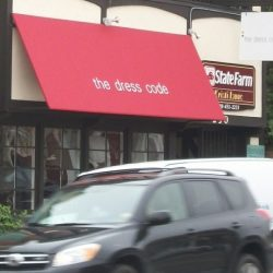 Red storefront awning with awning graphics for The Dress Code