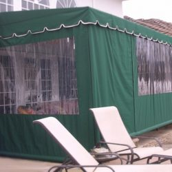 Residential drop-roll awning cover with green awning fabric