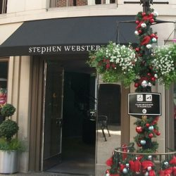 Dark storefront awning with white awning graphics for Stephen Webster