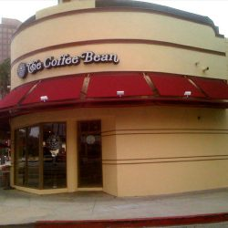 Custom storefront awning for The Coffee Bean with red awning fabric
