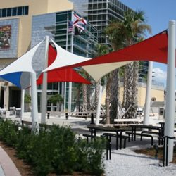 White, blue, red, and tan commercial sun shade panels for an outdoor area