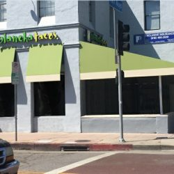 Light green and yellow storefront awning for Plancha Tacos