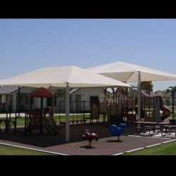 Large tension shade awning with white awning fabric for a playground