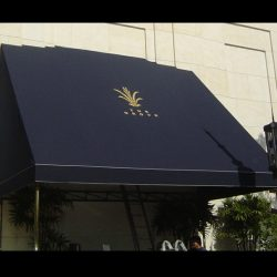 Commercial awning with black awning fabric and gold awning graphics for The Grove