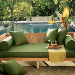 Green pad cushions on a wood frame for a pool area