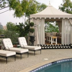 Custom pool cabana with beige awning fabric and custom drapes