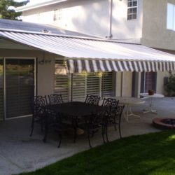 Residential retractable awning with striped awning fabric for a patio