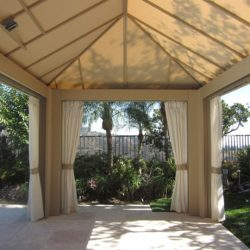Large cabana with beige awning fabric and custom outdoor drapes