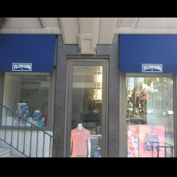 Blue window awnings with white awning graphics for Vilebrequin