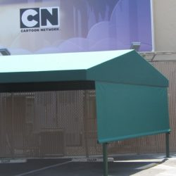 Custom green awning with drop-roll awning shade