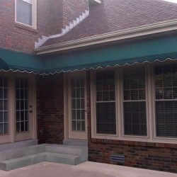 Green awning fabric on a custom residential entrance awning