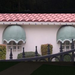 Residential dome window awnings with light green and white awning fabric