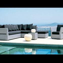 Black pad cushions on grey wicker next to a pool