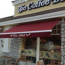 The Coffee Bean commercial retractable awning with red awning fabric and awning decals