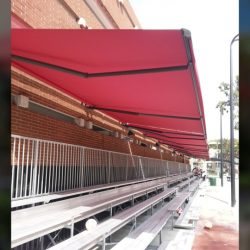 Commercial retractable awning with red awning fabric